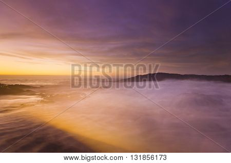 golden sunset at pacific ocean with white waves on rocky shore