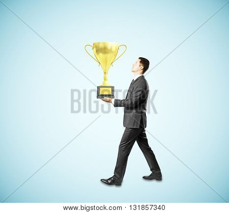 Businessman carrying golden cup trophy on blue background