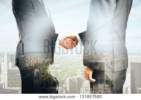 Businessmen shaking hands on city background. Double exposure