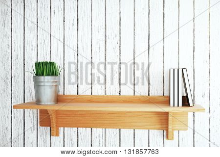 Wooden shelf with plant and book on grey plank background. Mock up 3D Rendering