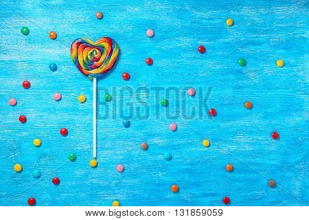 Flat Lay Of Beautiful Colorful Lollipop Shape Heart And Scattered Sweet Bonbons On Painted Blue Wood