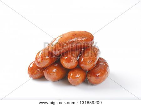 stack of grilled short sausages on white background