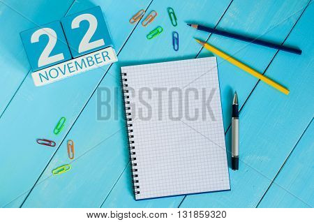 November 22nd. Image of november 22 wooden color calendar on blue background. Autumn day. Empty space for text.