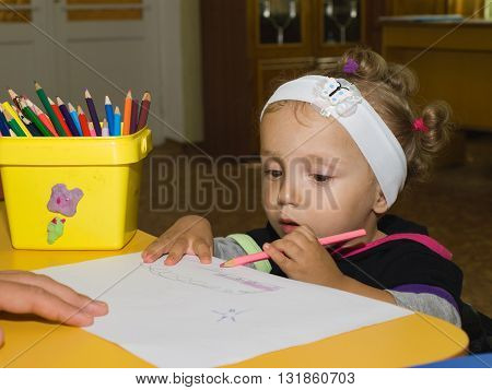 Little Girl Draws Pencil On Paper