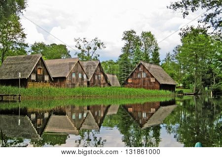 brown wooden boathouses reflecting in the water with reed and trees in the background