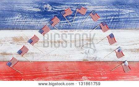 Small USA flags forming arch formation on red white and blue rustic boards. Fourth of July holiday concept for United States of America.