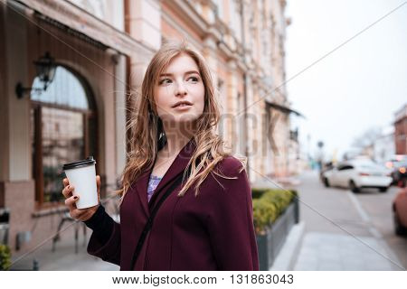Pensive pretty young woman drinking coffee on the street of the city