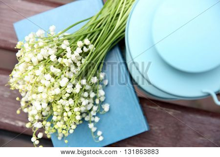 Bouquet of lilies of the valley on wooden bench