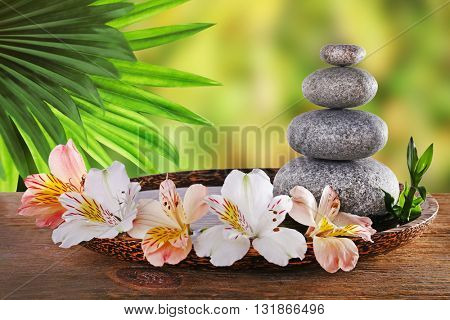 Composition with spa stones and alstroemeria on natural blurred background