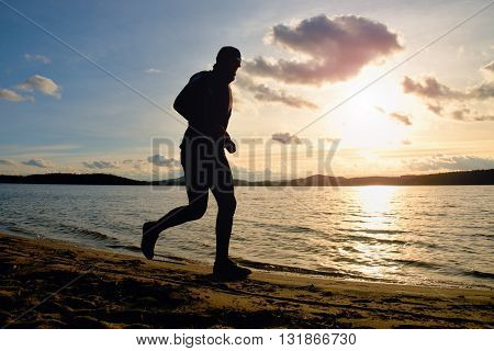 Tall Man With Sunglass And Dark Cap Is  Running On Beach At Autumn Sunset