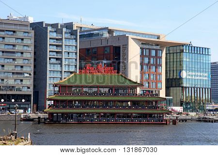 AMSTERDAM, NETHERLANDS - MAY 6, 2016: Chinese restaurant and modern buildings on canal Amsterdam, Netherlands.