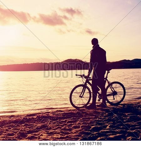 Silhouette Of Sportsman  Holding Bicycle On Lake Bech, Colorful  Sunset Cloudy Sky And Reflection In