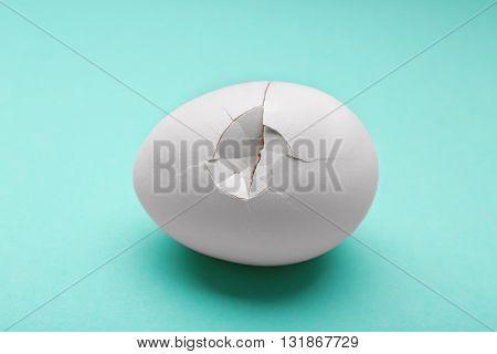 Cracked egg on turquoise background