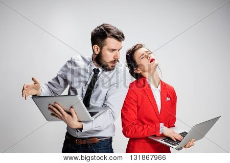 The vexed young businessman and businesswoman with laptops on gray background. The concept of relationship of colleagues.