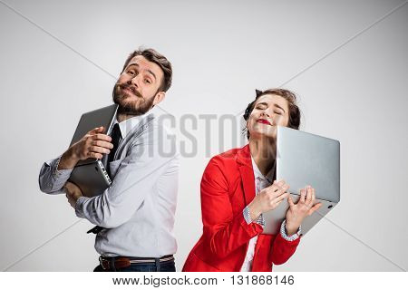 Love on the Internet. The young businessman and businesswoman with laptops on gray background