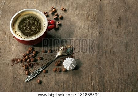 Cup of coffee with zephyr and spoon on wooden table