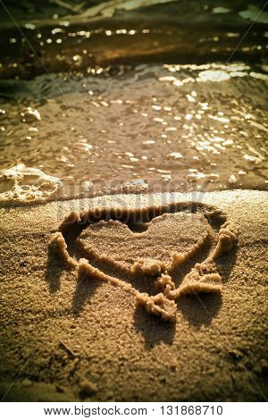 Lovely Small Heart Sketched In Salt  Sand At Beach. Evening Warm Colors Of Sunset Mirror In Water Le