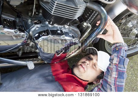 young mechanic repairing a vintage motorcycle in the garage