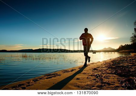 Silhouette of sport active adult man running and exercising on the beach. Calm water island and sunset sky background.