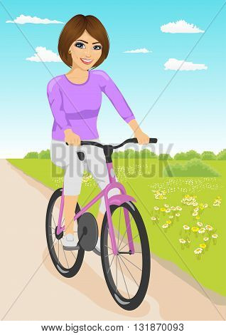 Young beautiful woman having fun riding a bicycle on a dirt road in countryside