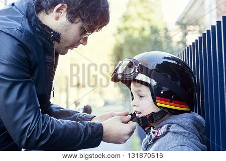 Young Loving Dad Fastens Helmet To His Son Before Travel