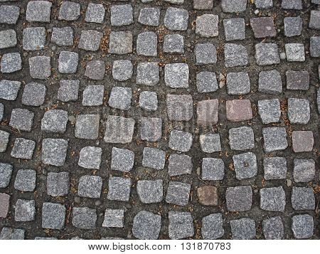 Gray square stones paved (causeway) road .