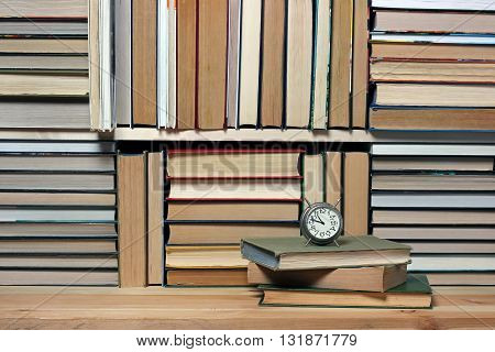 Retro alarm clock on a background of books. Book background. Books on the shelf library.
