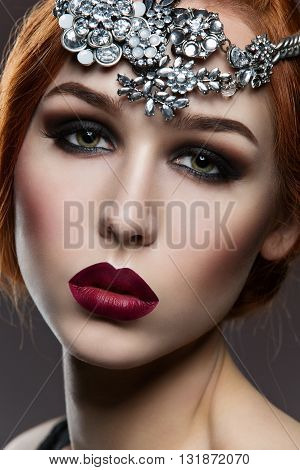 Beautiful young woman with dark makeup and big crystal accessory on head. Closeup beauty shot.