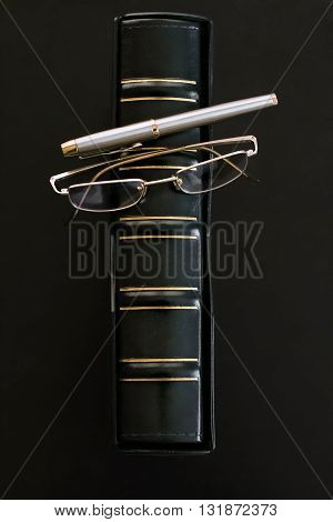 Book in leather green case glasses and fountain pen