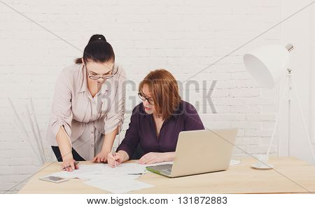 Two women in the office. Teamwork, colleagues, business communication. Working process. Middle-aged architects designers in team work discuss project. Start up discussion. Corporate female coworkers.