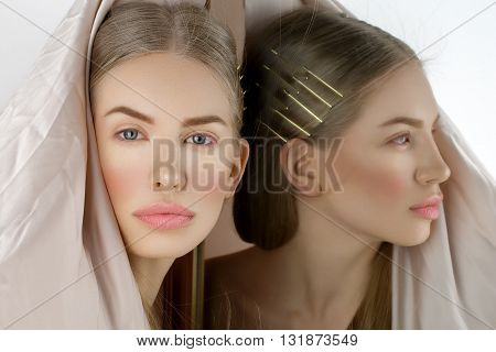 Beautiful young woman with blond hair and makeup covered with piece of creamy fabric. Copy space.