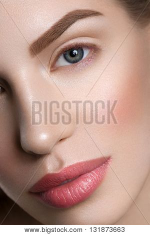 Beautiful young woman with blond hair and nude pink lips. Closeup beauty shot. Macro. Detail.