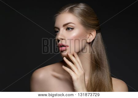 Beautiful young woman with blond hair and nude pink lips touching face. Over black background. Closeup beauty shot.