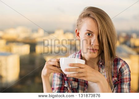 Hardworking hipster woman drinking coffee. Portrait of woman with cup of coffee. Concept of coffee in office people's lives