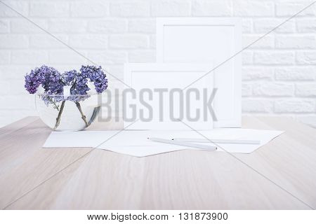 Lilac in bowl with water two blank picture frames paper sheets and pencils on wooden desktop and white brick wall background. Mock up