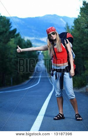 Pretty young woman tourist hitchhiking along a road.
