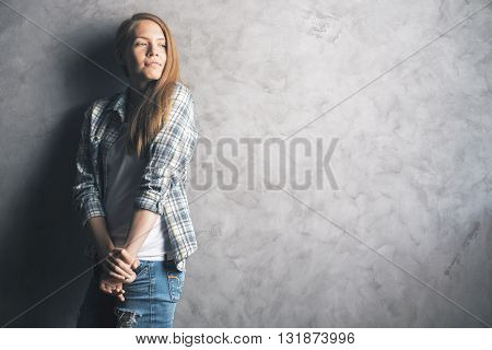 Casually dressed daydreaming young woman standing against blank concrete wall. Mock up