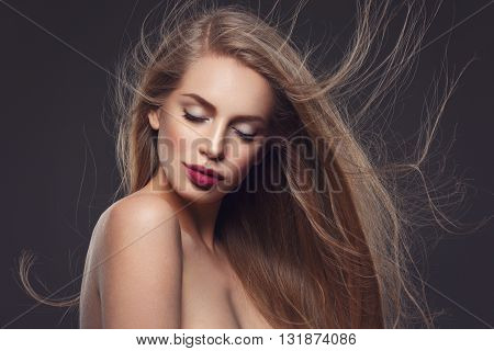 Beautiful young woman with natural makeup and blowing long blond healthy hair. Over dark grey background. Copy space.