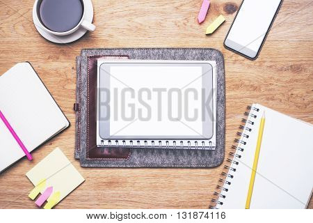 Topview of wooden table with blank tablet placed on grey case coffee smartphone and notepads with colorful stickers. Mock up