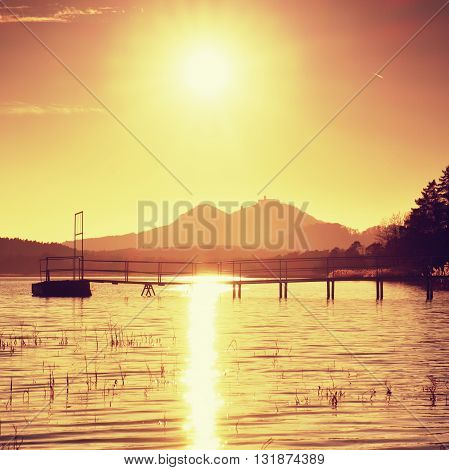 Colorful Autumn Sunrise At Coastal, Abandoned Wharf. Island With Stronghold At Horizon.