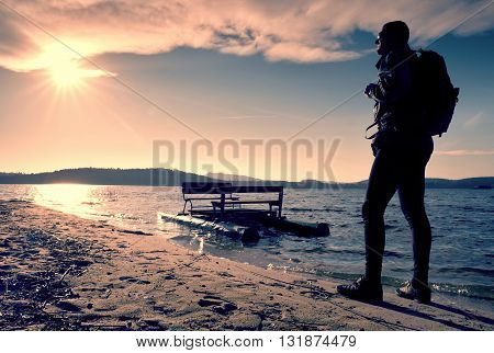 Tall Tourist Walk On Beach At Paddle Boat In The Sunset