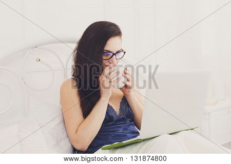 Middle aged woman with laptop in white bed. Woman in eyeglasses looks into gadget pc. Drinking morning coffee. Beautiful woman in blue nightwear at bed surfing internet at her computer. High key.