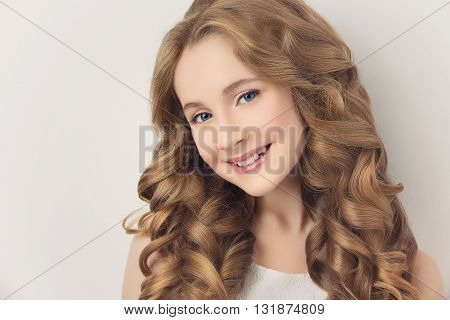 Beautiful teenage girl with long curly hair over white background. Copy space.