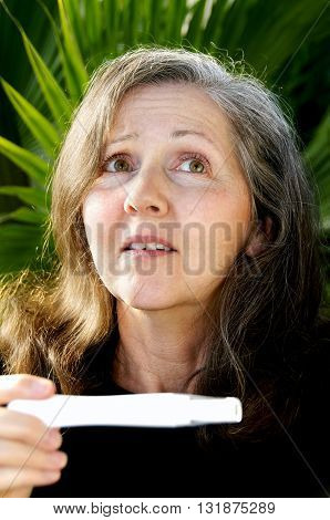Middle-aged woman looking up with a worried expression after seeing the results of a home pregnancy test.