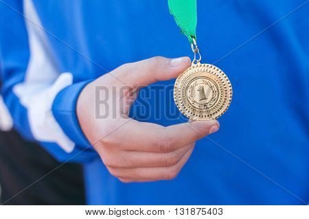 Hand of the man and medal close up. The winner holds a medal. Victory in competitions. First place. The hand holding a gold medal.