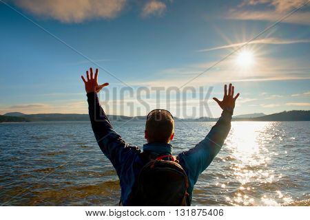 Short Hair Tourist In Blue Clothing With Hands In Air Along Beach With The Blue Sky In Background.