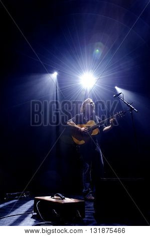 Musician playing a guitar on stage beneath a light that has a star effect.