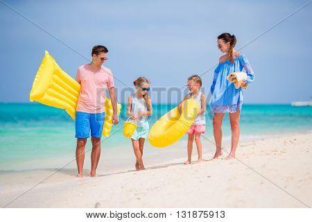 Happy beautiful family on white beach having fun