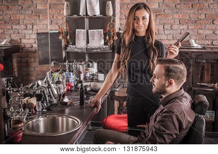Skillful female hairdresser hairstyle hair of attractive man in chair