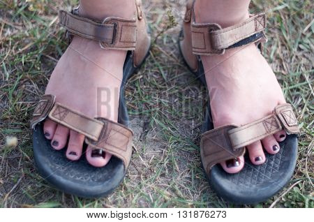 Closeup of stylish woman feet in large size men's sport sandals on the ground. Fiery fingernails. Outdoor fashion sport shoes footwear concept.